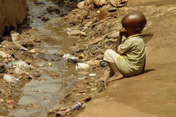 image of child near open sewer in Kampala. credit via flickr http://www.flickr.com/photos/gtzecosan/3110617133/